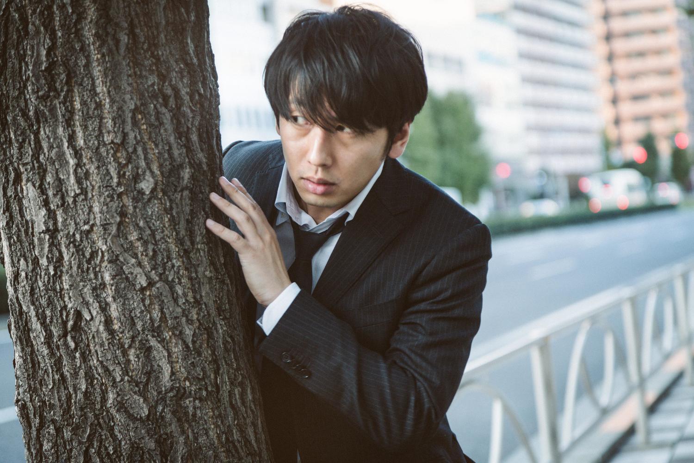 木の陰に隠れる男性