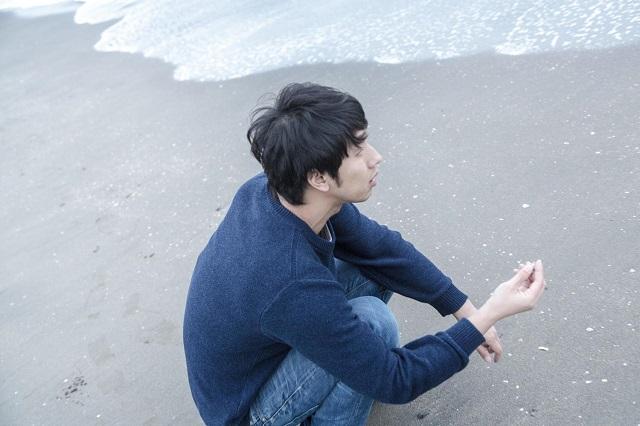 海辺でたそがれる男性