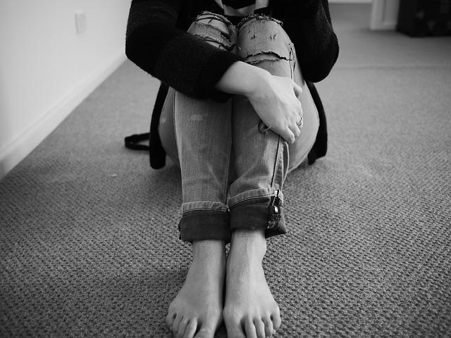 膝を抱えた女性