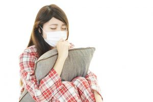 枕を抱えて咳き込む女性