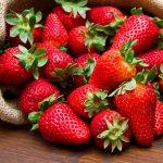 fresh strawberry in burlap sack on wood