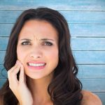 Composite image of pretty brunette with a toothache